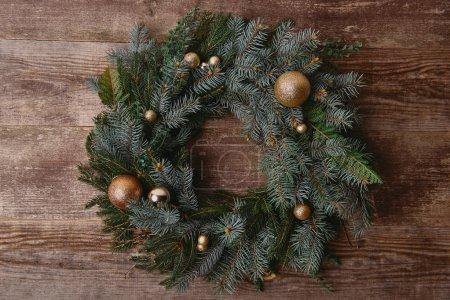 Foto de Vista elevada de corona de abeto de Navidad con juguetes en la mesa de madera - Imagen libre de derechos