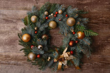 top view of Christmas fir wreath with baubles on wooden table