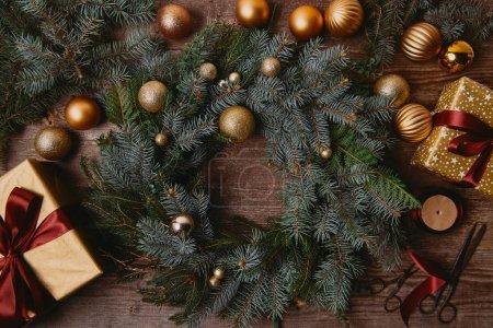 Foto de Vista superior de cajas de regalo de Navidad y la corona de abeto en mesa de madera - Imagen libre de derechos
