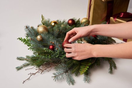 cropped image of woman decorating christmas fir wreath with toys isolated on white