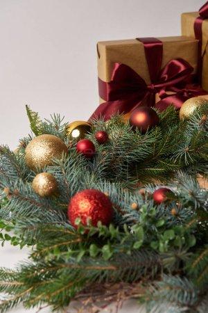 Foto de Corona de abeto de Navidad con adornos rojos y dorados, cajas de regalo aislados en blanco - Imagen libre de derechos