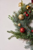 top view of christmas fir wreath with red and golden baubles isolated on white