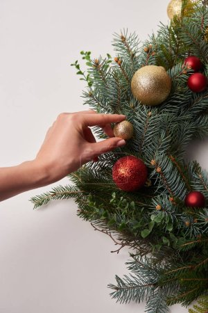 cropped image of woman putting small bauble on christmas fir wreath isolated on white