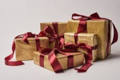 golden Christmas gift boxes with burgundy ribbons isolated on white