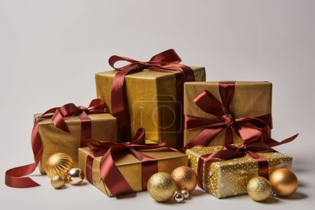 golden Christmas gift boxes with burgundy ribbons and baubles isolated on white