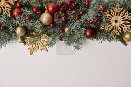 Photo for Top view of fir twigs with Christmas toys and golden snowflakes isolated on white - Royalty Free Image