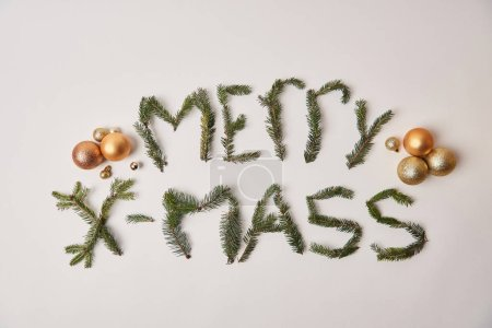 top view of greeting merry xmass made of fir twigs isolated on white