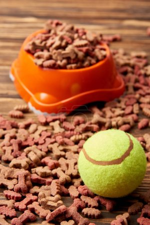 close up view of plastic bowl with dog food and ball on wooden table