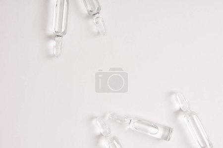 elevated view of ampoules with medical liquid on white surface