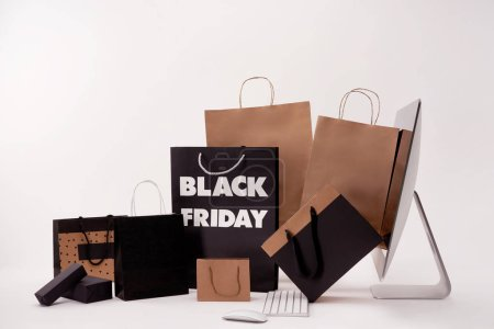 side view of computer and boxes with shopping bags with black friday sign on white