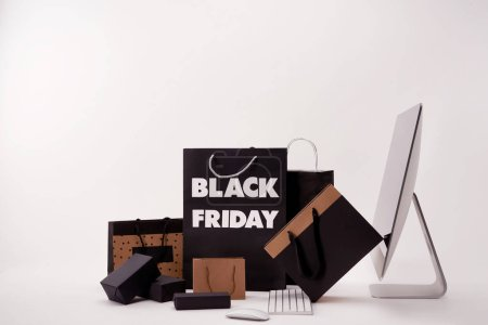 side view of computer and various boxes with shopping bags with black friday sign on white