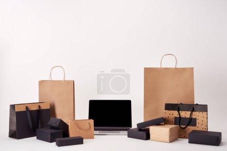 Photo pour Ordinateur portable avec écran blanc avec des sacs à provisions et des boîtes sur la surface blanche, concept du vendredi noir - image libre de droit