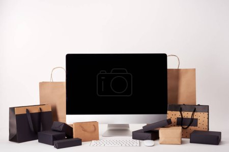 computer with blank screen with shopping bags and boxes on white surface, black friday concept