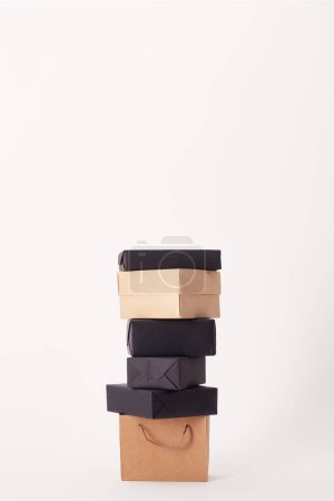 Photo for Shopping bag and stacked boxes on white surface, black friday concept - Royalty Free Image
