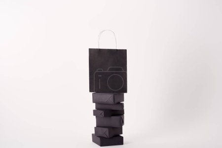 black shopping bag on stacked boxes on white surface, black friday concept