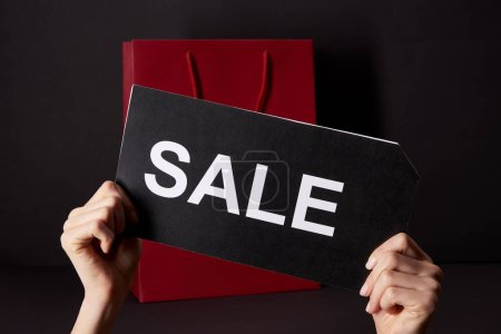 Photo for Cropped shot of woman holding banner with sale inscription in front of red shopping bag, black friday concept - Royalty Free Image