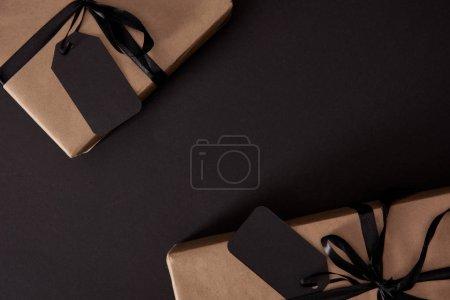 Photo pour Vue du dessus des cadeaux d'artisanat enveloppés avec des étiquettes noires sur la surface noire, concept du vendredi noir - image libre de droit