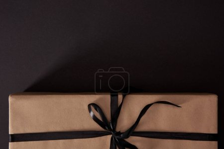 top view of craft wrapped gift box on black surface, black friday concept