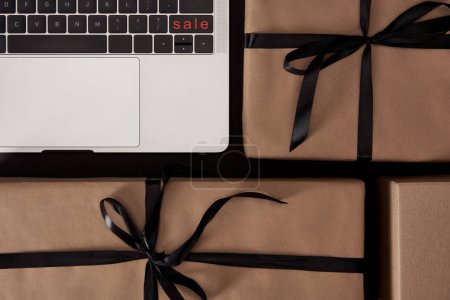 top view of craft wrapped gift boxes and laptop with black friday button on black surface