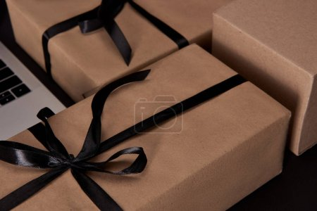 craft wrapped gift boxes with laptop on black surface, black friday concept