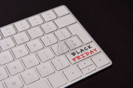 close-up shot of computer keyboard with black friday button isolated on black