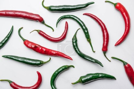 top view of red and green chili peppers on white marble surface