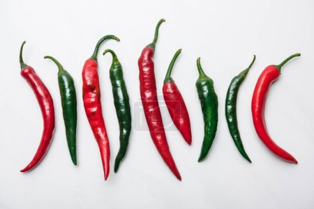 Photo for Top view of red and green chili peppers in row on white marble tabletop - Royalty Free Image