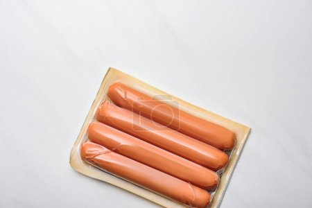 top view of plastic package of sausages on white marble surface