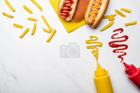 top view of hot dogs with mustard and ketchup on white marble surface
