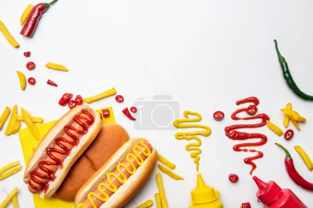 Photo for Top view of delicious hot dogs and fries with mustard and ketchup on white surface - Royalty Free Image