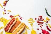 """Постер, картина, фотообои """"вид сверху вкусные хот-доги и картофель с горчицей и кетчупом на белой поверхности"""""""