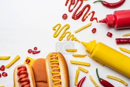top view of tasty hot dogs and fries with mustard and ketchup on white surface