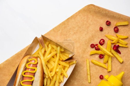 top view of tasty hot dog with fries on parchment paper isolated on white