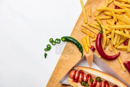 top view of spicy hot dog with fries on parchment paper isolated on white