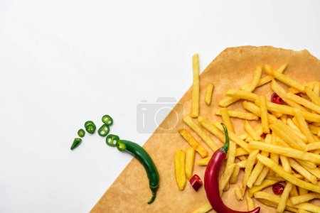 top view of french fries with spicy peppers on parchment paper isolated on white