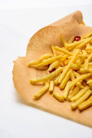 delicious french fries with spicy peppers on parchment paper on white