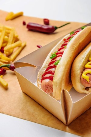 close-up shot of hot dogs in cardboard tray with french fries on parchment paper