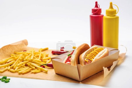 close-up shot of tasty hot dogs with french fries on paper and on white
