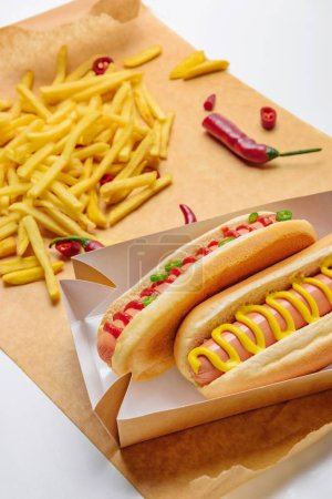 close-up shot of delicious hot dogs with french fries on parchment paper