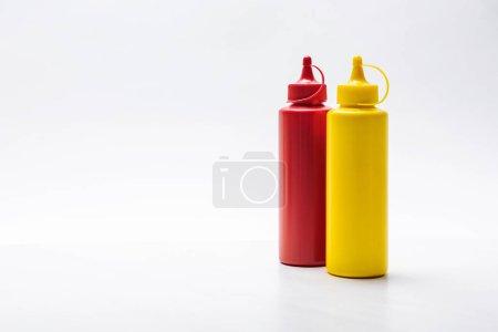 gros plan tiré de bouteilles de ketchup et moutarde sur surface blanche