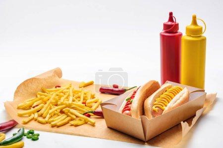 Photo pour Gros plan de délicieux hot-dogs à la moutarde et de ketchup sur papier avec des frites sur blanc - image libre de droit