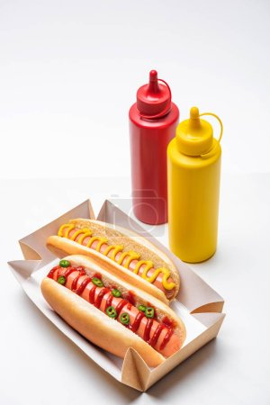 close-up shot of tasty hot dogs with mustard and ketchup on white
