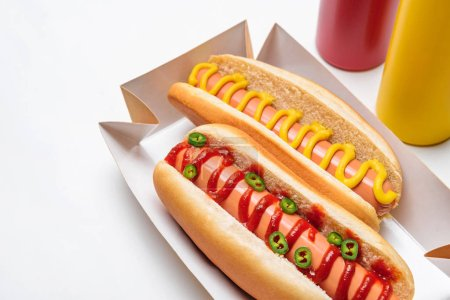 close-up shot of hot dogs with mustard and ketchup on white