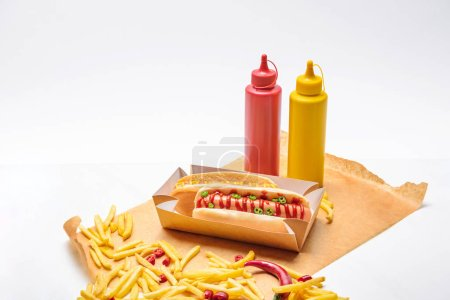 close-up shot of hot dogs with french fries, mustard and ketchup on paper on white surface