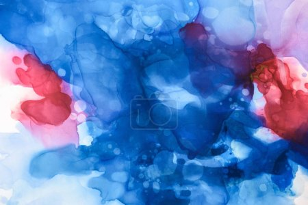 beautiful blue, red and violet splashes of alcohol inks as abstract backdrop