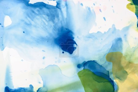 green and blue splashes of alcohol inks as abstract background