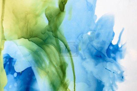leuchtend grüne und blaue Farbspritzer als abstrakter Hintergrund