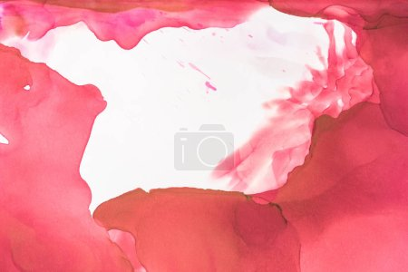 red and brown splashes of alcohol inks on white as abstract background