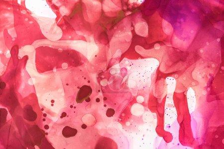 texturierte violette und rote Farbspritzer von Alkohol als abstrakter Hintergrund