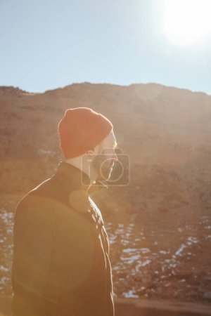 Photo for Handsome young man in red hat looking away in front of mountain on sunny day, Carpathians, Ukraine - Royalty Free Image